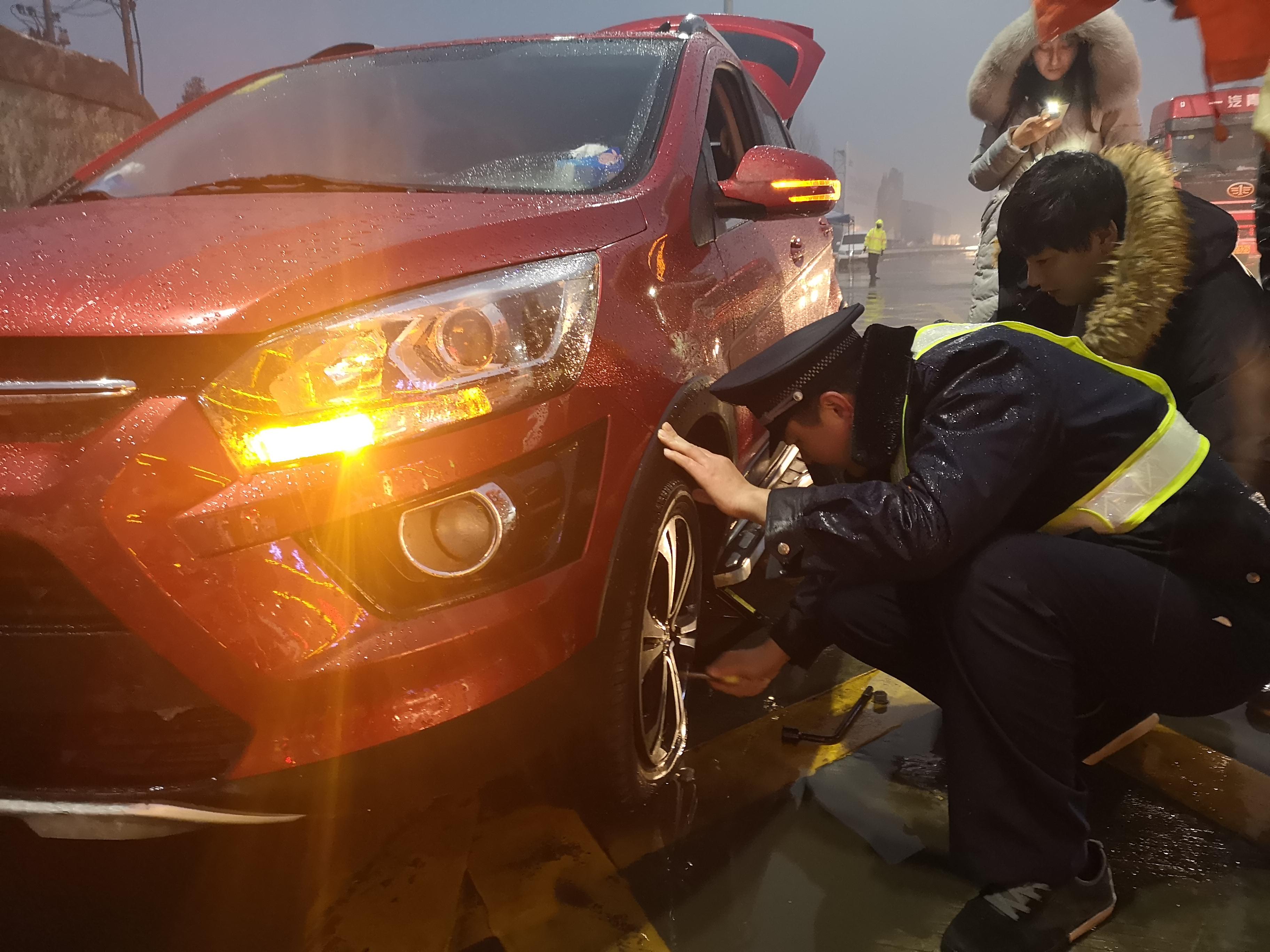 雪中送暖,郑新黄河大桥收费人员帮助抛锚车辆换备胎。.jpg